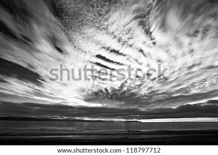 Dramatic clouds at sunset from a beach on the Kachemak Bay in Alaska in black and white.