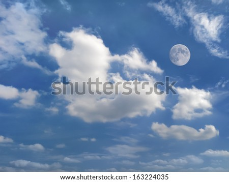 dramatic clouds moving across summer blue sky with moon