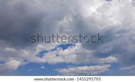 Dramatic cloudscape in high blue sky. White cumulus and grey stormy clouds background. Cloudy textures. Summer weather sky. #1455295793