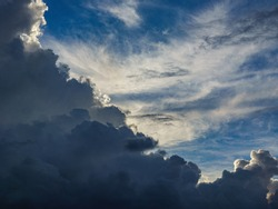 Dramatic cloudscape showing differences in altitude, type, density, and luminance of clouds near sunset in summer, west central Florida, for background or element with motifs of transition and change