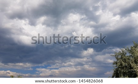 Dramatic cloudscape with green tree foliage in corner of frame. High overcast sky scenery with grey blue stormy clouds. Summer windy weather before thunderstorm. Cloudy background. #1454826068