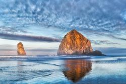 Dramatic coastal seascape featuring scenic rock formations in vivid sunrise colors. Location: Haystack Rock, Cannon Beach, Oregon, USA