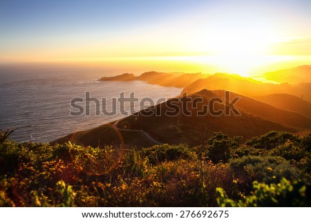 Dramatic coastal sunset with island peninsula and golden light ocean