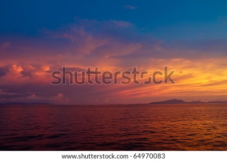 Dramatic colorful sunset on endless ocean horizon in Komodo National Park, Indonesia
