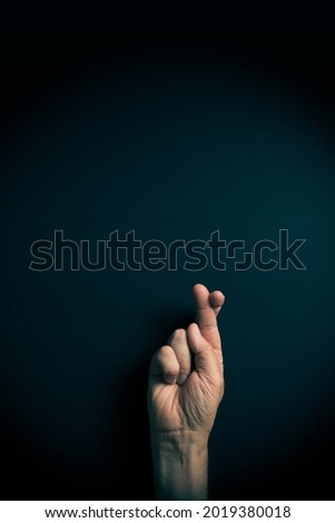Dramatic colour image of male hand demonstrating ASL American sign language letter R with empty copy space for editors Stok fotoğraf ©