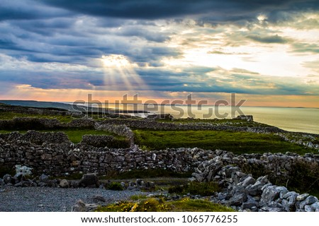 Dramatic colourful sunst at Aran Islands, Ireland with enlightingly bright god rays coming through clouds and rural farming area and stone fences in the foreground