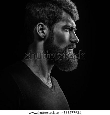 Dramatic concept Black and white close-up portrait of young handsome bearded man looking forward. Studio shot on black background