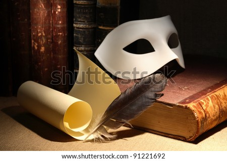 Dramatic concept. Vintage still life with quill and scroll near mask and old books on dark background