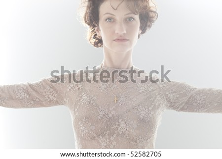 Dramatic cropped portrait of woman indoors with arms outstretched