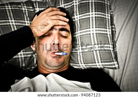 Dramatic desaturated image of a sick man laying in bed with fever