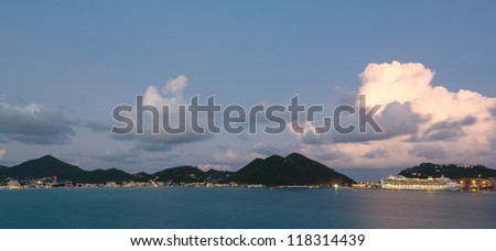 Dramatic evening sunset image of cruise ship in town of Philipsburg in Sint Maarten or Saint St. Martin in Caribbean