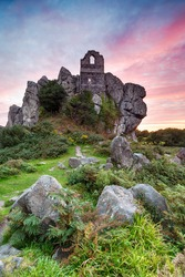 Dramatic fiery sunset over Roche Rock, a craggy outcrop of granite with the ancient ruin of a chapel built in to the rock, near St Austell in Cornwall