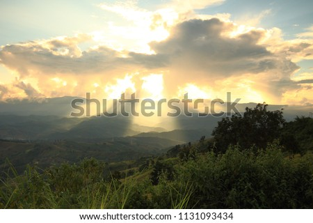 Dramatic god lights passing through clouds and shining on mountain ranges. warm light shower. God hope and dream concept