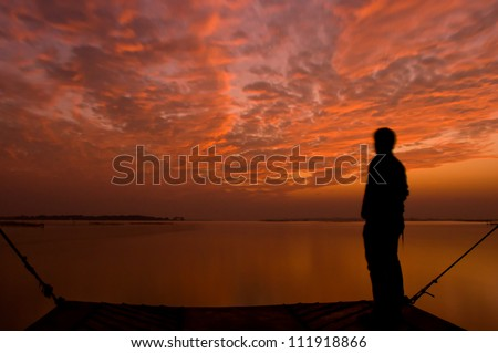 Dramatic golden orange sunset with a silhouette of a man, over Asia's largest salt water lake in Chilika, India