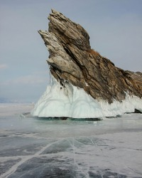 Dramatic graphical gray rock sharp texture white coastal splash ice Ogoy island Baikal lake Russia. Snow field landscape. Winter clouds overcast Visited popular innocent Tourism journey.