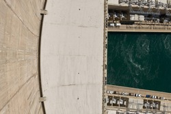 Dramatic High Angle View Looking Down Curved Wall at Green Water of Colorado River and Hydroelectric Equipment from top of Hoover Dam, Arizona Nevada Border, USA