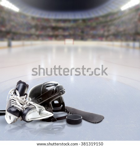Dramatic Hockey arena full of fans in the stands with helmet, skates, stick and puck on reflective ice and copy space. Deliberate focus on equipment and shallow depth of field on background.