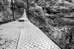 dramatic image of a cable walk bridge on rio Ocoa, dominican republic, in the Ocoa province with rocks and river 50 feet below.