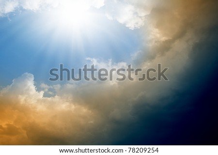 Dramatic impressive background -  blue sky with bright sun, dark clouds