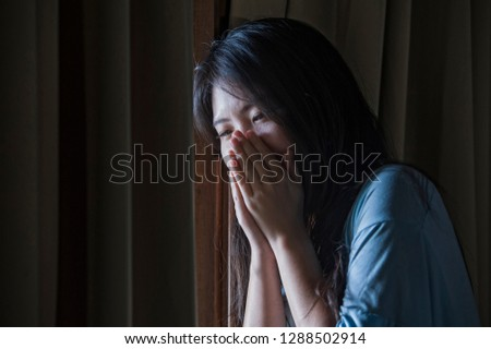 dramatic indoors portrait of young sad and depressed Asian Chinese woman crying desperate broken heart suffering depression and anxiety in dark light at home curtains window in sadness concept #1288502914