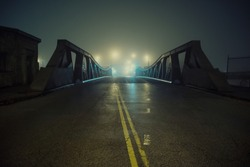 Dramatic industrial vintage river road bridge street scene at night with illuminating fog in Chicago.