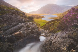 Dramatic landscape at Cwm Idwal in the Gyderau mountains of Snowdonia National Park in North Wales during sunset or sunrise.