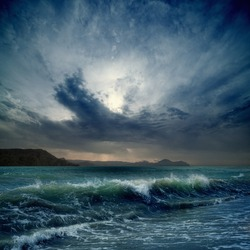 Dramatic landscape - dark stormy sky, sea waves, mountains