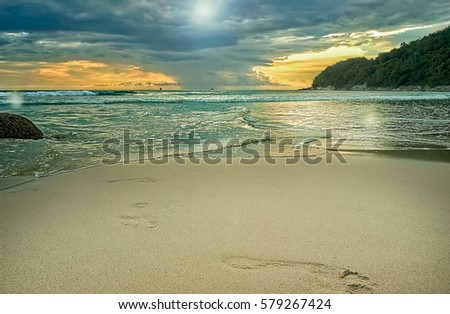 Stock Photo Dramatic landscape of the beach and sea at sunset on a background of storm clouds