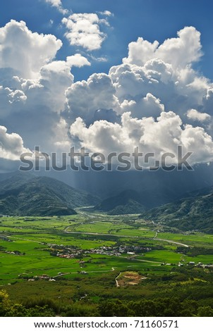Dramatic landscape of town under cloudy sky in daytime.