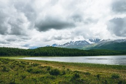 Dramatic landscape with mountain lake and forest on hills in sunlight and snowy mountains in low clouds in changeable weather. High mountains in cloudy sky and lake near green grasses and forest hills