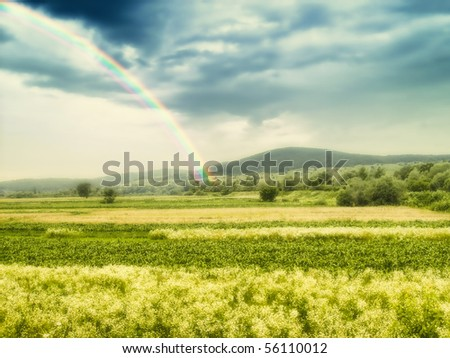 Dramatic landscape with rainbow over fields, raining in the distance