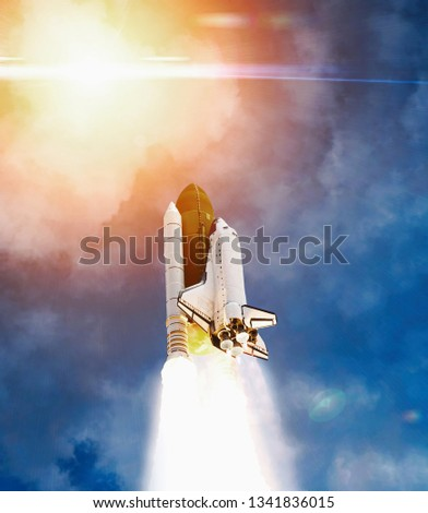 Dramatic launch. Rocket launching. Blue sky. CLouds and sun flare. Elements of this image furnished by NASA. #1341836015