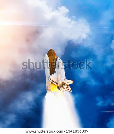 Dramatic launch. Rocket launching. Blue sky. CLouds and sun flare. Elements of this image furnished by NASA. #1341836039