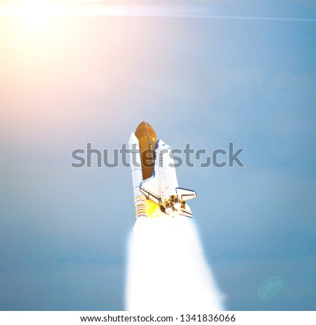 Dramatic launch. Rocket launching. Blue sky. CLouds and sun flare. Elements of this image furnished by NASA. #1341836066