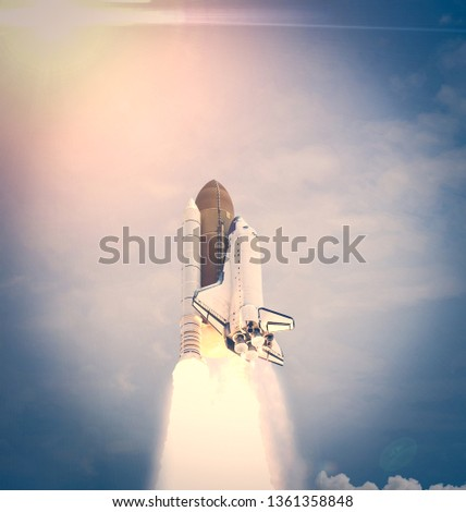Dramatic launch. Rocket launching. Blue sky. CLouds and sun flare. Elements of this image furnished by NASA. #1361358848