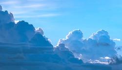 Dramatic light and dark cumulonimbus and cumulus clouds in blue sky background at evening time