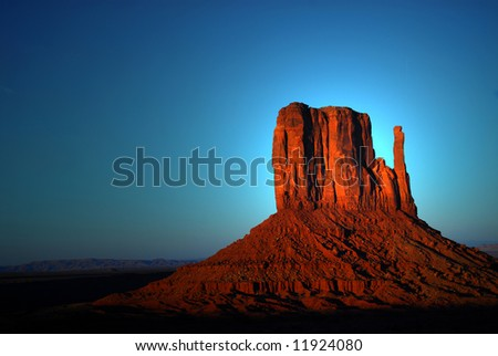 Dramatic light of dawn striking a rock formation in the Navajo nation land of Monument Valley