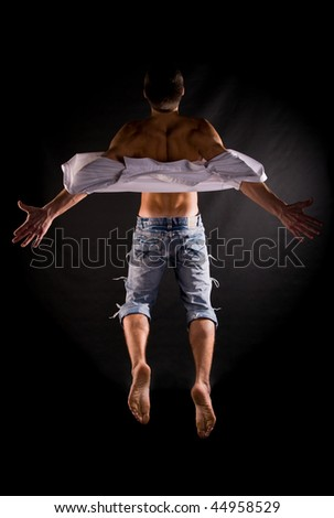 ... of modern acrobat jumping in front of black background - stock photo