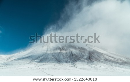 Dramatic misty snowcapped mountain landscape. Cloudy white mountains, with mysterious feel. Mystic, extreme adventure concepts. Shot in Bolivia Chile border crossing. Nature picture.