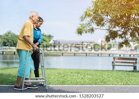 dramatic moments of young Asian carer assisting elderly or disabled using assistive walking devices, and always showcase inclusivity and acceptance when possible while spending time together on park