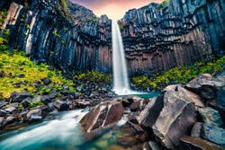 Dramatic morning view of famous Svartifoss (Black Fall) Waterfall. Colorful summer sunrise in Skaftafell, Vatnajokull National Park, Iceland, Europe. Artistic style post processed photo.