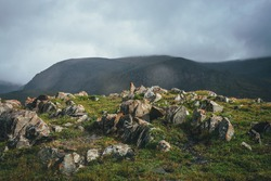 Dramatic mountain landscape with sharp stones with orange lichen on green hill under cloudy sky in rainy weather. Atmospheric alpine scenery with pointy rocks on hill under low clouds in overcast sky.