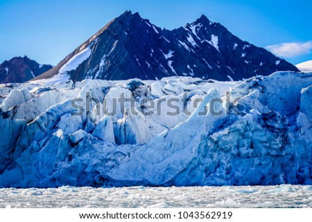 Dramatic mountains rise out from behind a cracked glacier in Svalbard in the Norwegian high arctic #1043562919