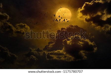 Dramatic mystical background - glowing full moon rises, flock of crows flies in dark sky. Elements of this image furnished by NASA