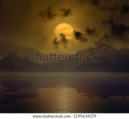Dramatic mystical background - rising orange full moon in dark night sky with reflection in water. Elements of this image furnished by NASA