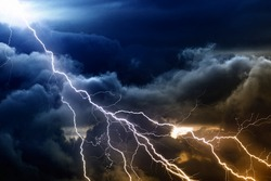 Dramatic nature background - bright lightnings in dark stormy sky