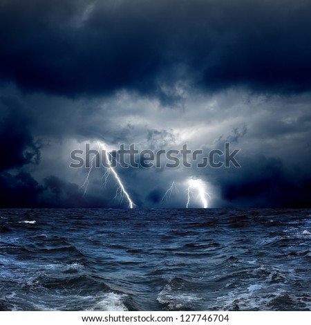 Dramatic nature background - lightnings in dark sky, stormy sea