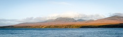 Dramatic panorama view on Isle of Jura coastline, from Isle of Skye, Scotland, sunset time, hills covered with cloudy sky