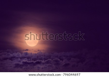 Dramatic photo illustration of a nighttime sky with brightly lit clouds and large, bright full moon. Toned. A great background. #796044697