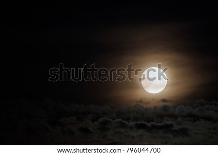 Dramatic photo illustration of a nighttime sky with brightly lit clouds and large, bright full moon. A great background. #796044700